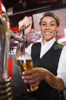 hübsche Bardame, die ein halbes Liter Bier zieht foto