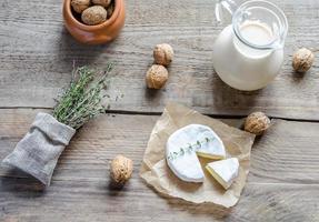 Camembert mit Krug Milch und ganzen Nüssen foto