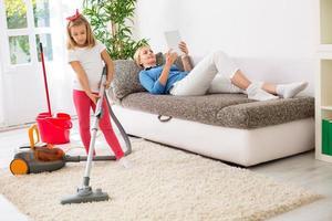 faule Mutter mit Tablette, während trauriges Mädchen Haus putzt foto