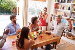 Freunde sitzen an einem Esstisch und feiern einen Geburtstag foto