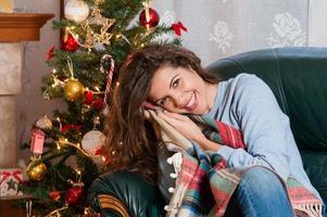 glückliche junge Frau, die auf Couch sitzt, die ein Kissen hält foto