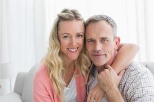 Porträt eines liebenden Paares, das auf Couch sitzt foto