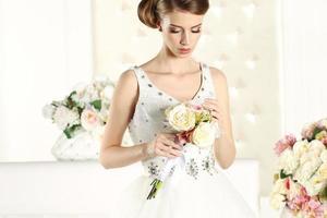 wunderschöne Braut in einem weißen Raum, posierend foto