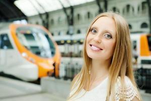 Frau wartet Zug am Bahnhof