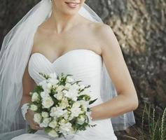 Porträt der schönen Braut mit Blumenstrauß in den Händen. foto