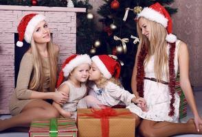 glückliche Familie, die neben einem geschmückten Weihnachtsbaum aufwirft foto