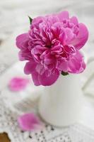 rosa Pfingstrose im Krug auf Vintage Spitzentischdecke foto