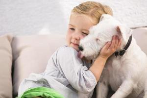 junges Mädchen, das ihren Hund auf der Couch umarmt foto