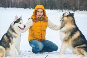Mann, der mit Hund Winterzeit mit Schnee geht