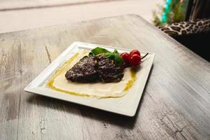 Gegrilltes Rindersteak und Champignons mit Tomaten auf weißem Teller