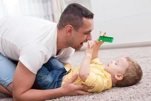 Der hübsche junge Vater verbringt Zeit mit seinem Kind foto