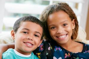 zwei junge Geschwister sitzen auf einer Couch und umarmen sich foto