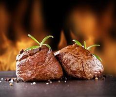 frische Rindersteaks auf schwarzem Stein und Feuer foto