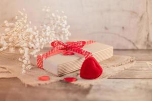 Valentinstagsgeschenk und Herzdekorationen auf Holz foto