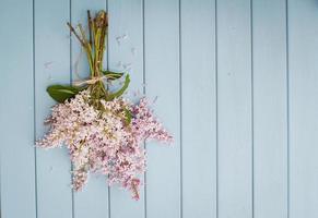 Blumenstrauß von Flieder auf dem alten blauen hölzernen Hintergrund
