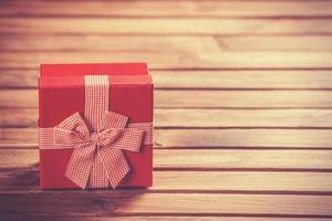 rote Geschenkbox auf Holztisch. foto