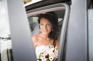 Nahaufnahmeporträt einer hübschen schüchternen Braut im Autofenster foto
