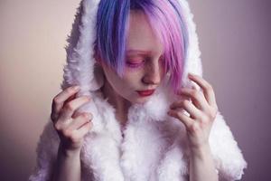 ungewöhnliches Mädchen mit rosa Haaren, fühlen sich kalt im Pelzmantel foto