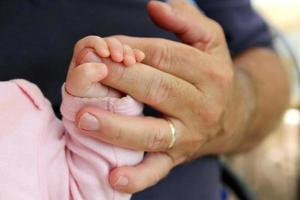 Neugeborenes Mädchen, das Opas Hand hält foto