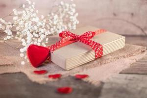 Valentinstagsgeschenk und Herzen auf Holz foto