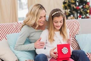 Tochter, die Weihnachtsgeschenk mit Mutter öffnet foto