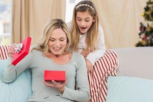 Mutter öffnet Weihnachtsgeschenk mit Tochter foto