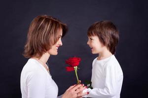 Junge, die seiner Mutter eine wunderschöne rote Rose gibt
