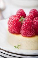 Käsekuchen mit frischen Himbeeren auf einem weißen Teller. Dessert. foto