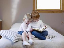 Schwestern lesen Buch auf dem Bett