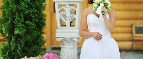 junge elegante Braut, die schönes Hochzeitskleid trägt. foto