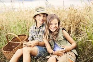 Freunde, die zusammen auf einem Weizenfeld picknicken foto
