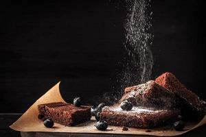 Schokoladen-Brownie mit Puderzucker horizontal bestreuen foto