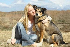Frau, die deutschen Schäferhund draußen umarmt foto