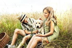 Bruder und Schwester auf einem Weizenfeld mit einem Hund foto