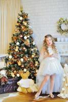 entzückendes Mädchen durch den Weihnachtsbaum