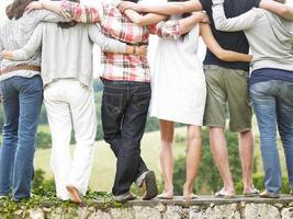 Rückansicht von Freunden, die auf Steinmauer stehen foto