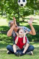 glücklicher Vater, der mit seinem Sohn am Ball spielt foto