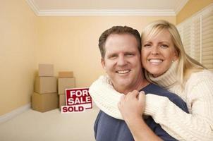 Paar in neuem Haus mit Kisten und verkauftem Verkaufsschild foto