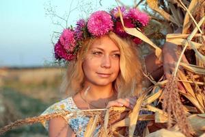 junge Frau im Maisheuhaufen mit Kranz