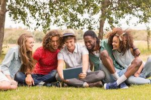 glückliche Freunde im Park, die Tablette betrachten foto