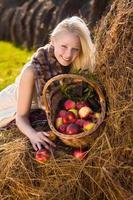 schöne blonde lächelnde Frau mit Äpfeln im Korb am Bauernhof foto