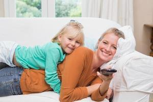 glückliche Mutter und Tochter, die fernsehen foto