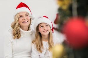 festliche Mutter und Tochter lächeln am Baum foto