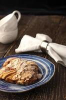 Croissant auf Keramikplatte mit verschwommenen Tassen und Serviette foto