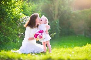 glückliche Mutter und ihre kleine Tochter mit Blumen im Garten
