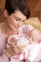 Porträt der Mutter, die Neugeborenes Baby zu Hause füttert foto