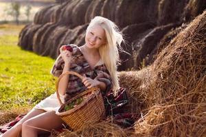 schöne blonde Frau mit Apfel auf Heuhaufen am Bauernhof foto