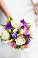 Hochzeitsstrauß mit verschiedenen Blumen in den Händen der Braut foto