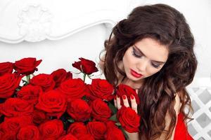 Nahaufnahmeporträt der brünetten Frau mit dem roten Rosenstrauß, foto