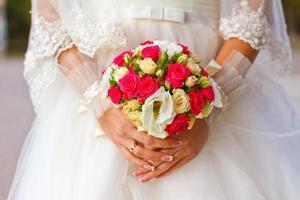 Braut, die Hochzeitsstrauß nah oben hält foto